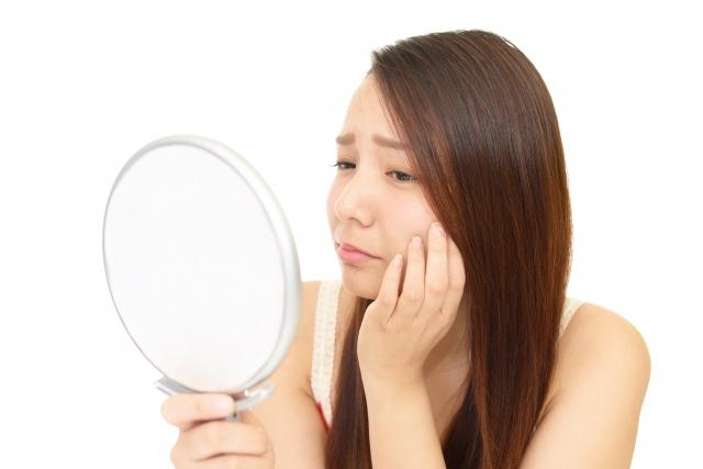 鏡を見て肌を気にしている女性