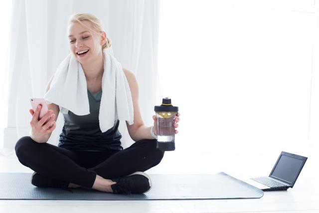 マットの上に座ってトレーニングの休憩をする女性