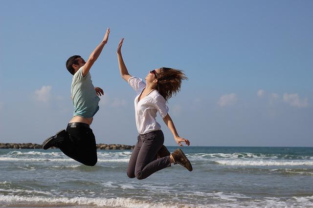 海辺でジャンプしながらハイタッチをする男女