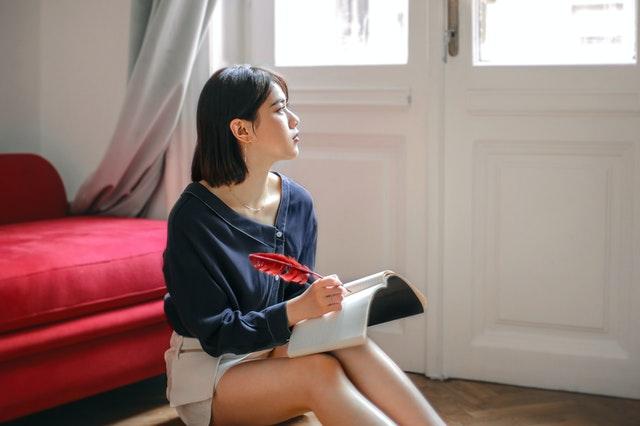 部屋でノートに書き記す女性