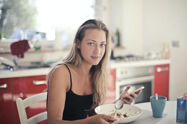 オートミールを食べるタンクトップの女性