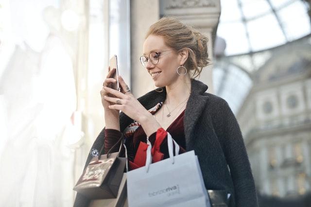 スマホを見ながら笑顔でショッピングを楽しむ女性